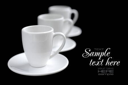 saucers: Empty white coffee cups and saucers on black background
