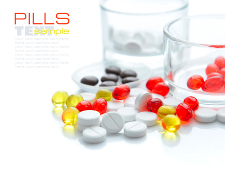 pilule: Heap of colorful pills and glass on a white background