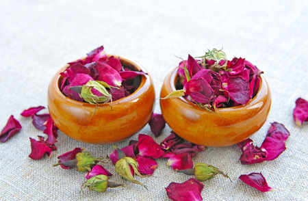 traditional healer: Dry healing flowers and petals in a cups on sackcloth, herbal medicine