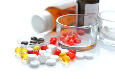pilule: Colorful pills are with glass and bottles on a white background