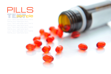 pilule: Pills pouring out of the brown bottle on a white background