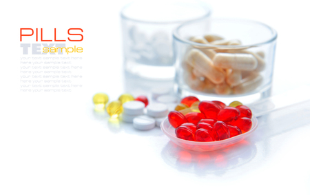 pilule: Red capsules are in a spoon on a background the color capsules Foto de archivo