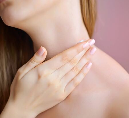 beauty care: Unrecognizable female person apply cosmetic cream on her neck Stock Photo