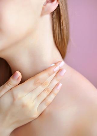 Unrecognizable female person apply cosmetic cream on her neck Stock Photo