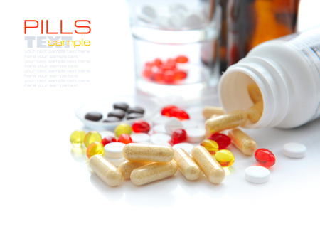 pilule: Capsules that pour out from a bottle on a white background Foto de archivo