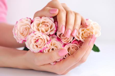 Handen van een vrouw met roze rozen tegen witte achtergrond