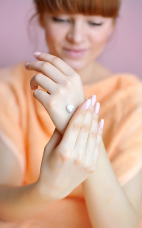 beauty care: Young woman applies cream on her hands after bath. Focus on hands Stock Photo