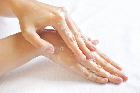 sudsy: Washing woman hands on a background a white towel Stock Photo
