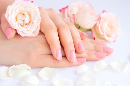 Handen van een vrouw met roze manicure op nagels en rozen