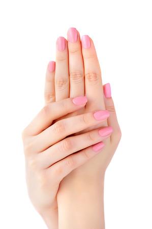 Close-up van de handen van een jonge vrouw met roze manicure op nagels geïsoleerd op een witte achtergrond