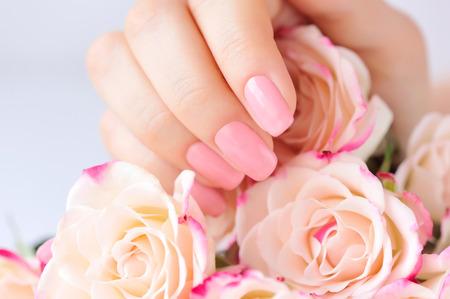 mujer con rosas: Manos de una mujer con la manicura de color rosa en rosas nailsand