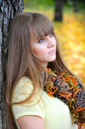 sad teenager: A portrait of young beautiful woman is in an autumn park Stock Photo