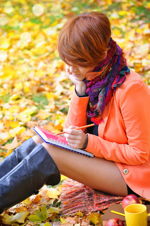 redhaired: Red-haired student girl with notebook on a background autumn leaves