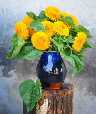 the milk jug: Decorative sunflowers are in a ceramic milk jug Stock Photo