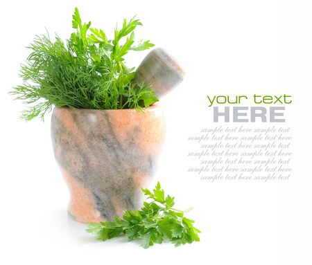 herbalist: Stone mortar and pestle with greenery of parsley and dill on white background Stock Photo