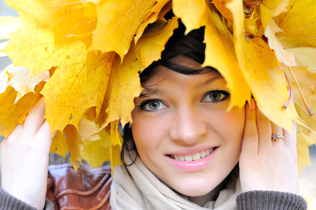chaplet: Girl in autumn in a chaplet from maple leaves Stock Photo