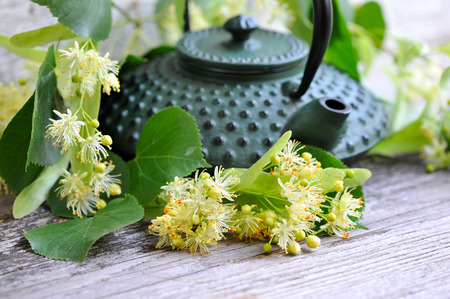 linden tea: Teapot with linden tea and flowers on old wooden background Stock Photo