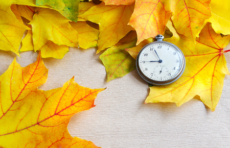 second meal: An old clock is on autumn maple leaves Stock Photo
