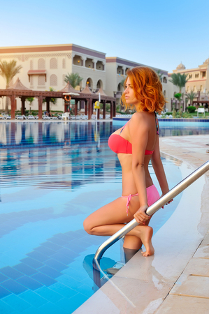 enters: Sexy of a beautiful redheaded girl who enters the water in the pool