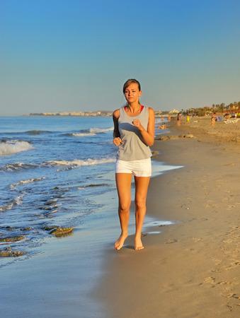 Beautiful girl running on beach at morning