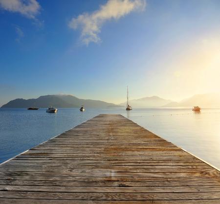 Zonsopgang boven de pier op de Egeïsche zee, ochtend aan de zee ligplaats Stockfoto