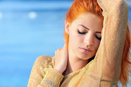 redheaded: Portrait of a young redheaded woman against the backdrop of the sea