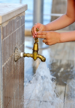 Close-up kid hands closes the faucet. Old grunge tap in garden Stock Photo