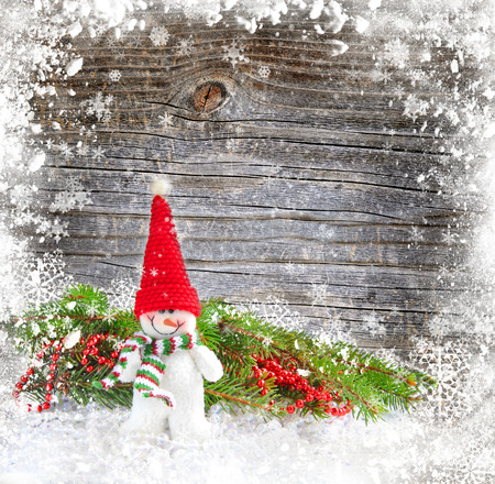 snowbound: Snowman with the branches of fir on a snowbound wooden background