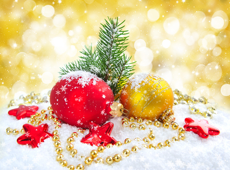 Christmas decorations of bauble with the sprig of fir on snow