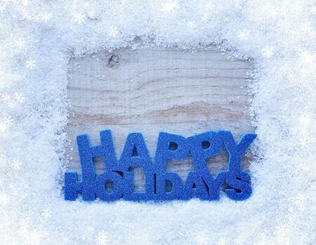 spangle: The frame of the snow and the inscription Happy Holidays on a wooden background with space for your text