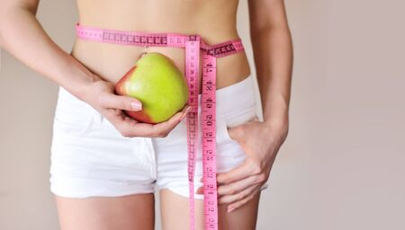 waistline: Young woman is measuring body and hold apple