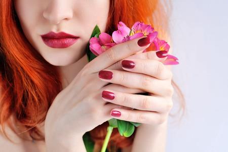 Mooie roodharige jonge vrouw met bloemen alstroemeria. Focus op handen