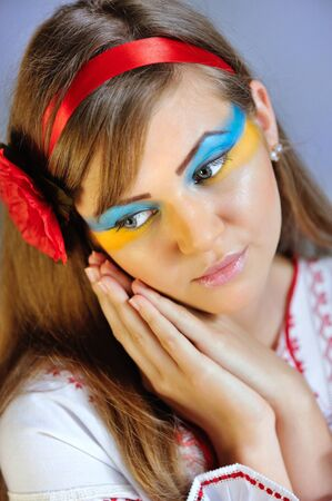 Portrait of a woman with creative makeup Ukrainian flag on her face in the Ukrainian national costume