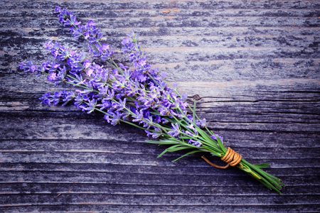 Lavender flowers (Lavandula) on an old wooden background. Art photo in purple tone.