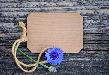 Paper tag with fresh cornflowers (Centaurea cyanus) on wooden table. Top view.