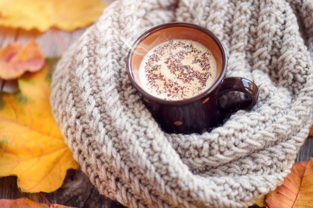 Autumn leaves, hot cup of coffee and a warm scarf on wooden table background. Morning coffee, sunday relax and still life concept.
