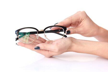 oculista: Female hands holding eye glasses on white background Foto de archivo