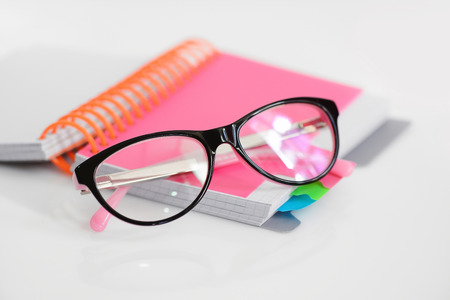Eye glasses with pink spiral notebook on white background Stock Photo