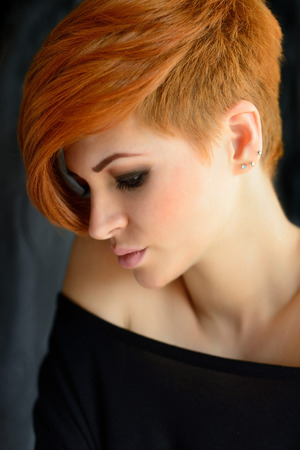 Portrait of a beautiful young red-haired woman with short hair on a dark background 版權商用圖片
