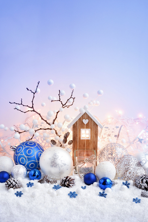 Christmas composition with decorative balls and toy house on snow. Christmas greeting card. Space for your text. Stock Photo