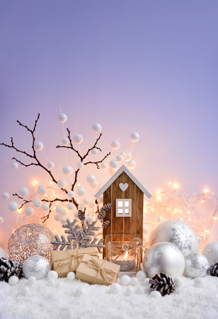 Christmas composition with decorative balls, toy house and candle on snow. Christmas greeting card. Space for your text.