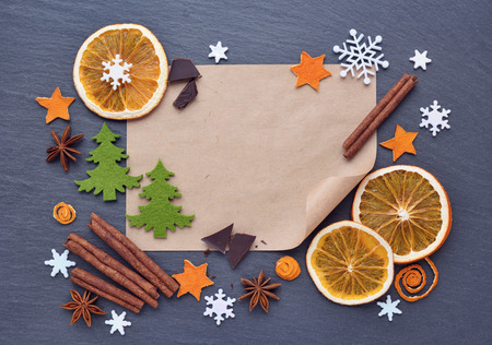 Christmas background with gingerbread cookies, snowflakes, spices, chocolate and blank sheet of paper for your congratulations on dark table, top view