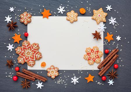 ジンジャーブレッドのクッキー、雪の結晶、スパイスと暗い表、平面図にお祝いしていただき用紙の空白のシートでクリスマスの背景 写真素材