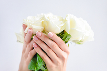 Hands of a woman with beautiful french manicure and bouquet of white roses Stock Photo