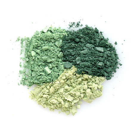 Mixed color eye shadow crushed samples on white background. Top view