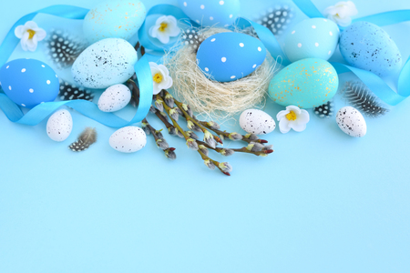Easter eggs and and willow branches on blue background. Easter card with empty space for text Stock Photo
