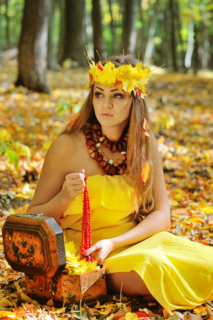 Portrait of a beautiful girl in a wreath of autumn leaves Imagens