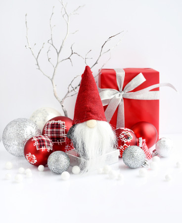 Christmas composition with gnome, gifts and festive decorations on a white background. 版權商用圖片
