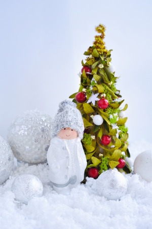 Decorative little boy figure and christmas tree with festive decorations оn the snow. New Year greeting card. 免版税图像
