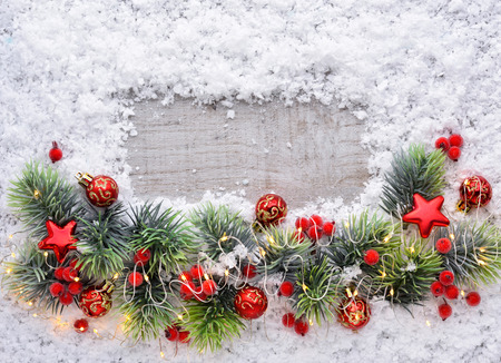 Christmas decorations and spruce branches on snow-covered a wooden background. Top view, copy space. Christmas or New Year greeting card. Stock Photo